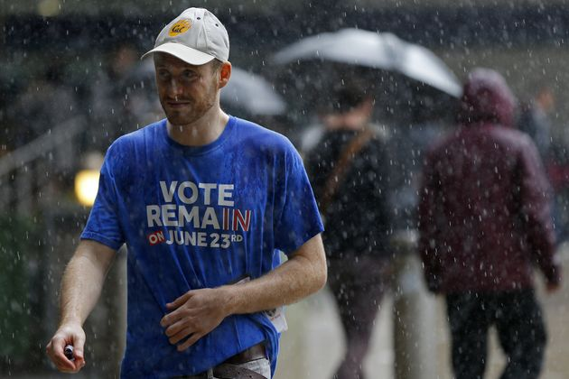 A man wearing a 'Vote Remain' t-shirt walks in the rain in central