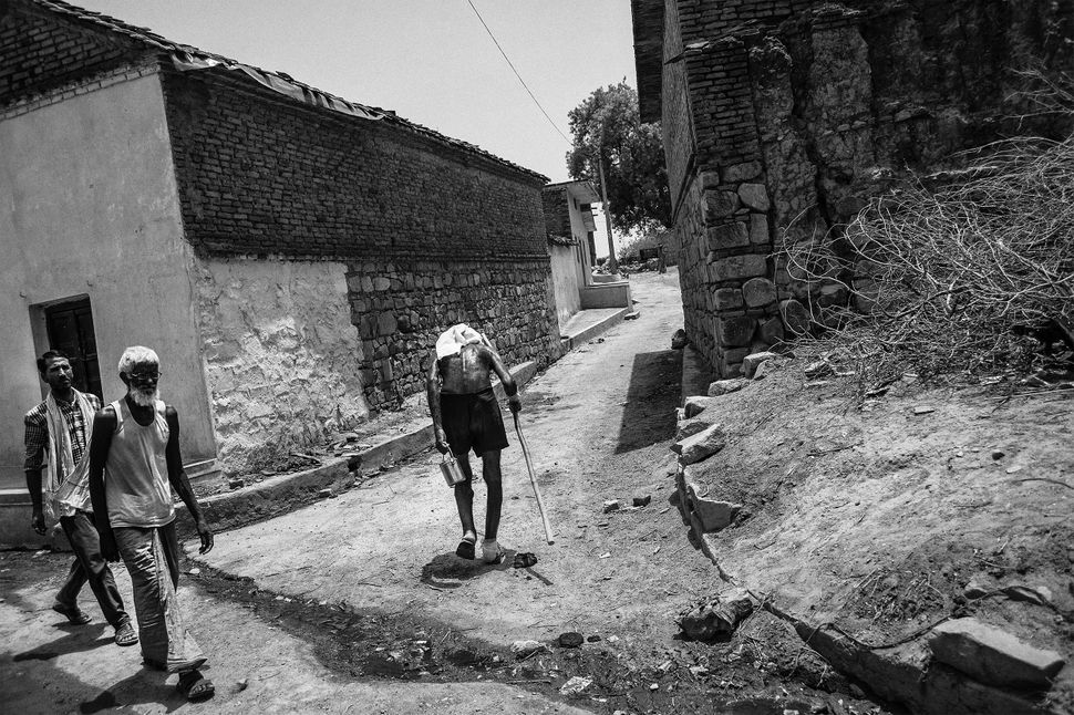 Weighed down by the burden of successive droughts, Narain Singh walks along a narrow village lane.