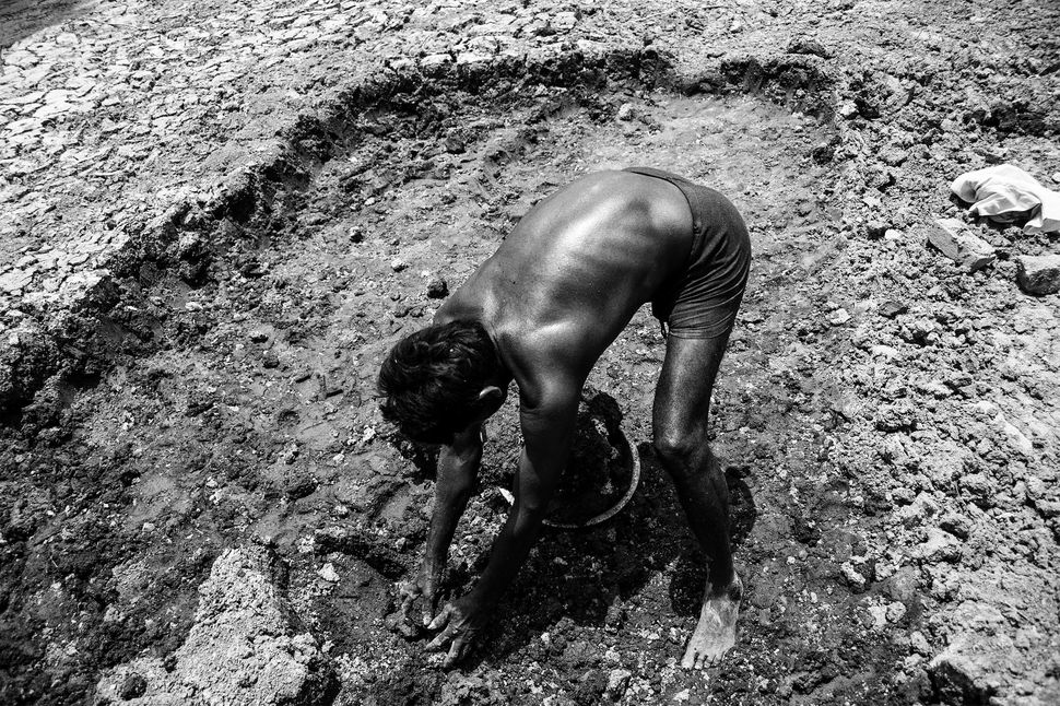 Dayaram digs out dirt from the bottom of a dry pond near Dhikwaha.