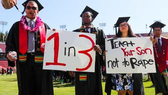 Stanford students John Lancaster Finley(L) and Brandon Hill(C) carry signs during the 'Wacky Walk' to show their solidarity for a Stanford rape victim during graduation ceremonies at Stanford University, in Palo Alto, California, on June 12, 2016.  / AFP / GABRIELLE LURIE        (Photo credit should read GABRIELLE LURIE/AFP/Getty Images)