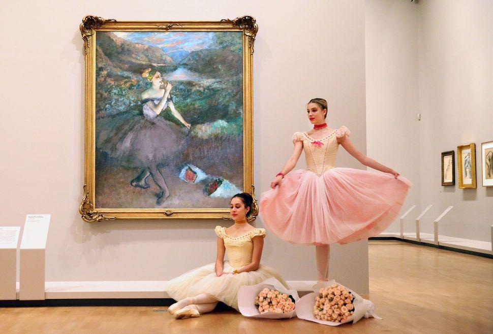 Evie Ferris and Georgia Scott-Hunter, Artists of The Australian Ballet, pose next to one of Edgar Degas' iconic ballet dancer