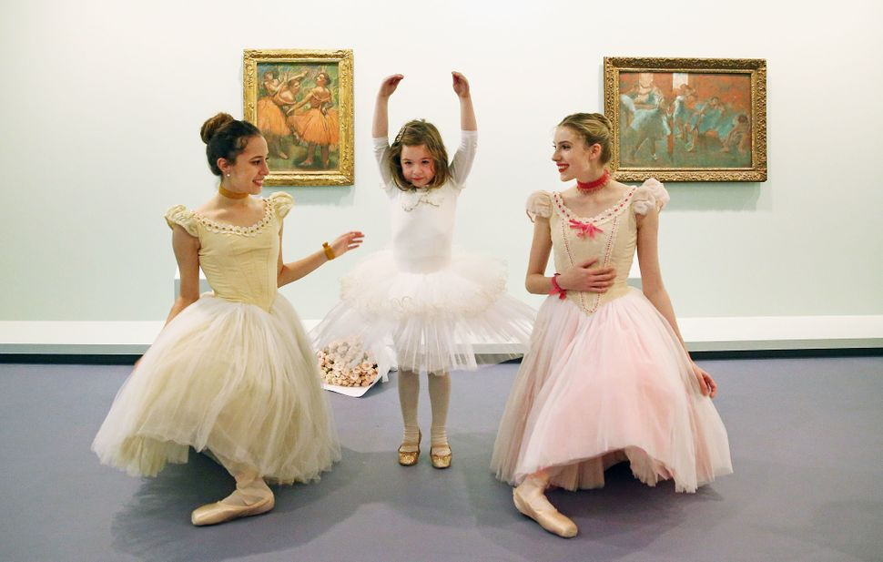 Six-year old ballerina Mena Deboil dances with Evie Ferris and Georgia Scott-Hunter, artists of The Australian Ballet, next t