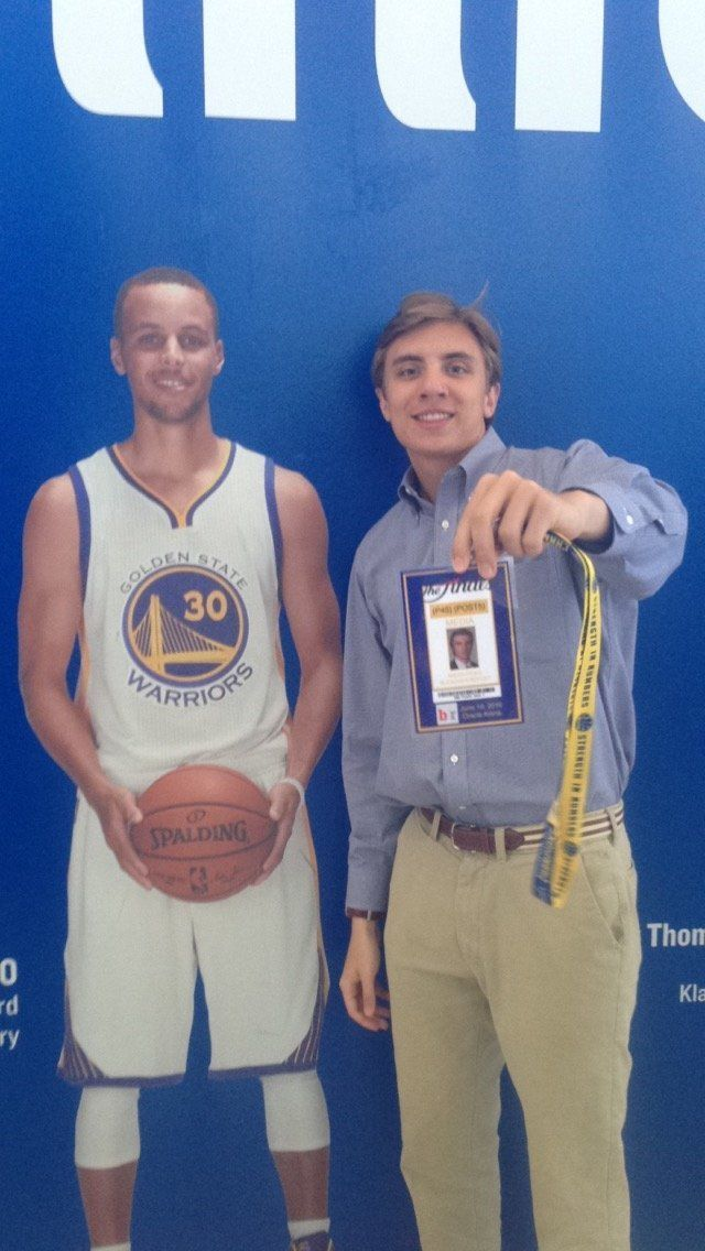 Micah Poag poses with his fake press pass and an image of Steph Curry.