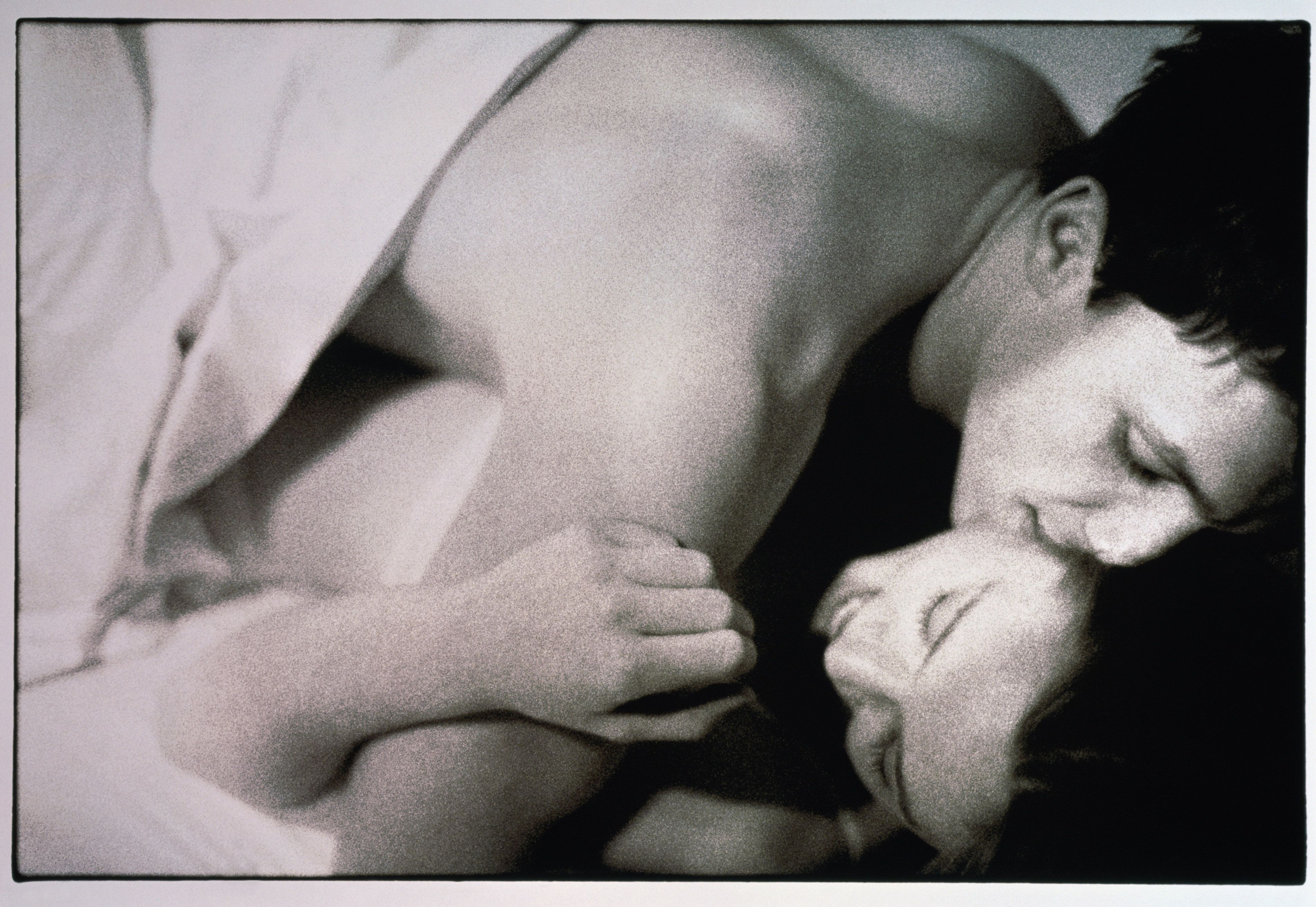 Couple embracing in bed (toned B&W)