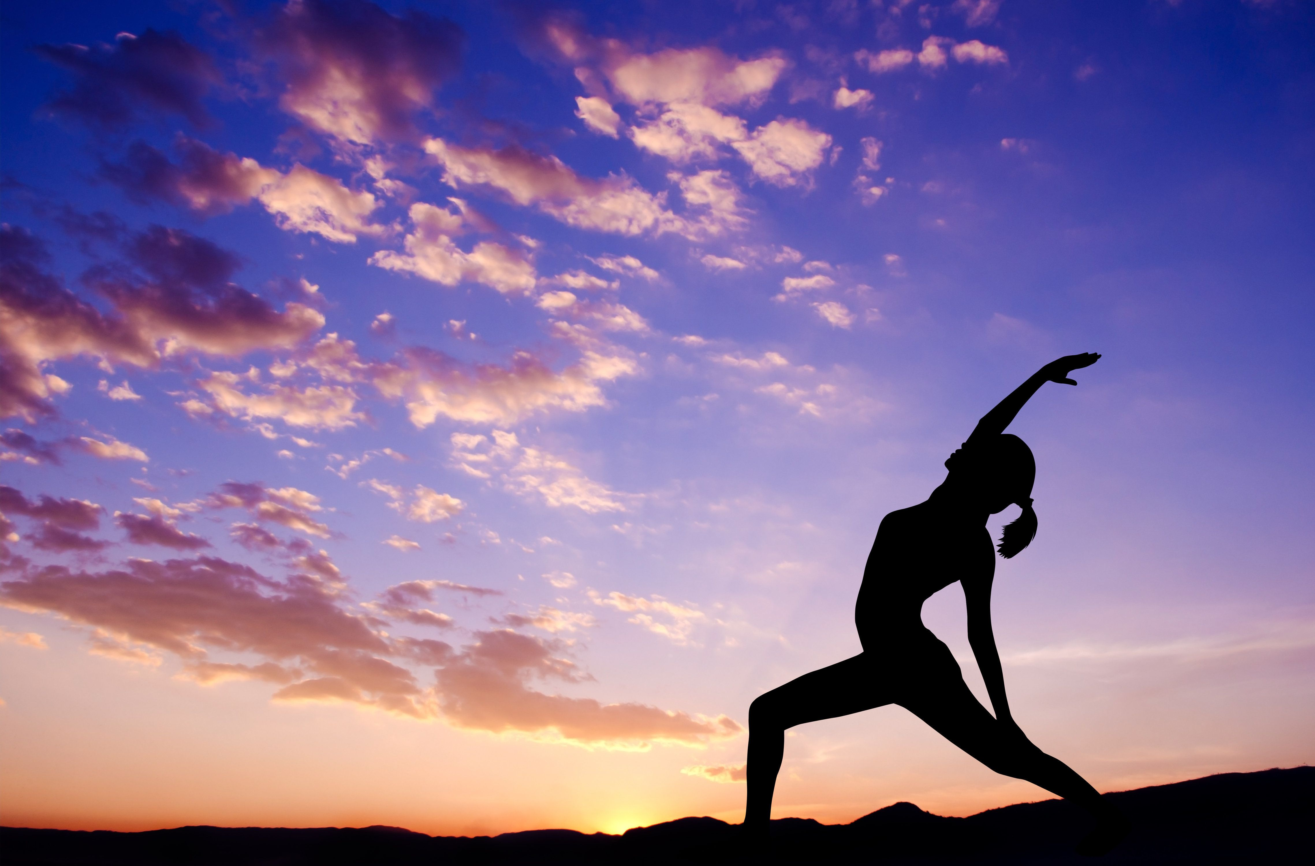 Silhouette of healthy woman doing yoga meditation during sunrise with natural sunlight outdoor.
