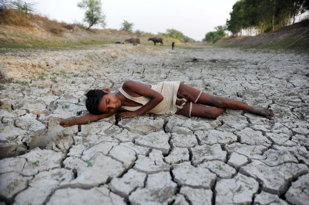 A child lies down on a dry bed of parched mud that is the dried up River Varuna at Phoolpur. Much of...
