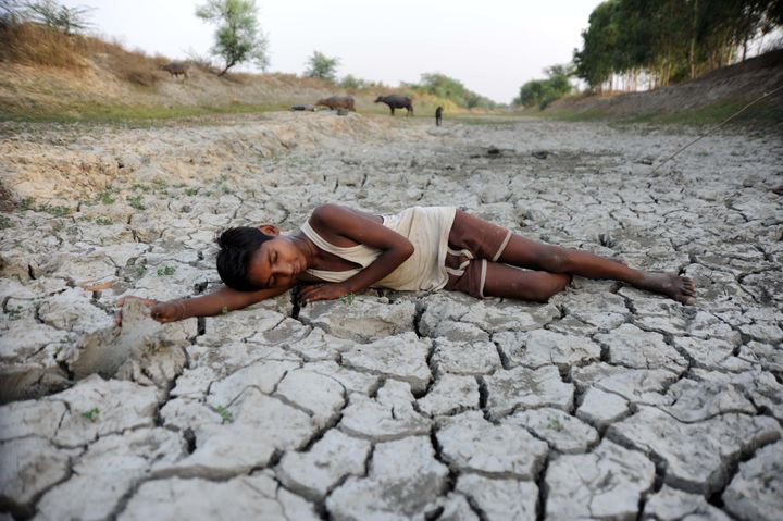 A child lies down on a dry bed of parched mud that is the dried up River Varuna at Phoolpur. Much of India is reeling from a