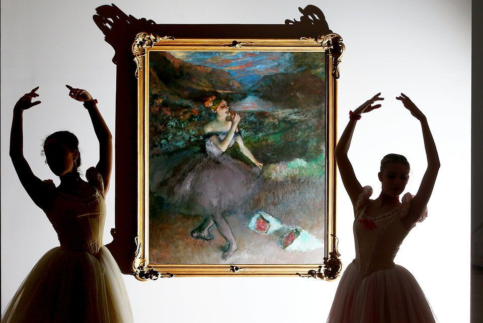 Ballerinas from The Australian Ballet are silhouetted as they pose next to one of Edgar Degas iconic ballet dancer paintings