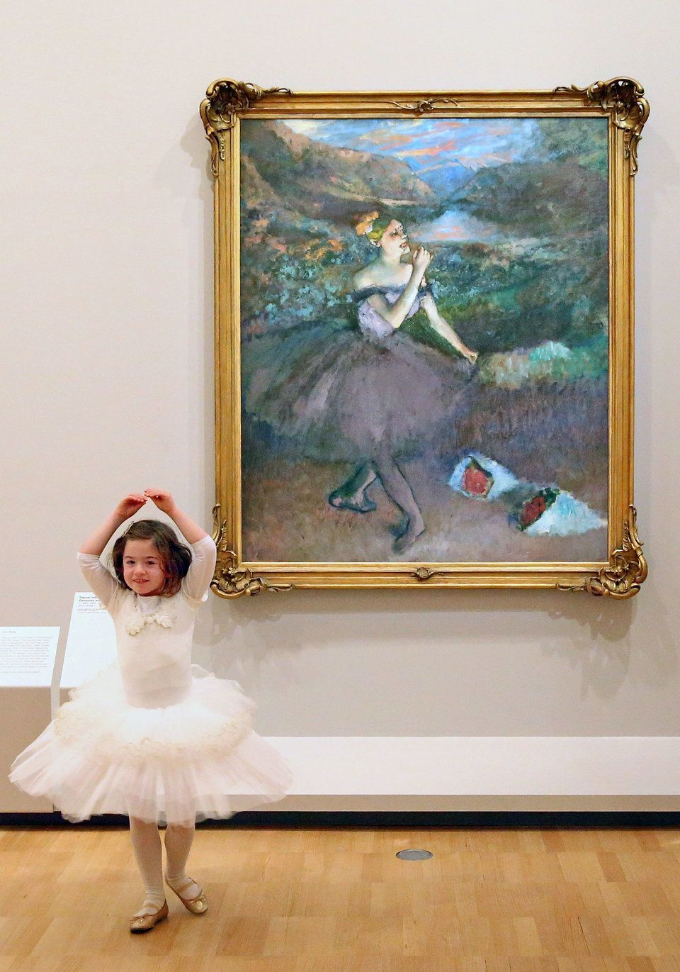 "Six-year old ballerina Mena Deboil dances next to one of Edgar Degas' iconic ballet dancer paintings ""Dancer with Bouquets."""