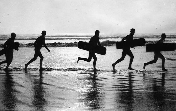 Surfers on the way to the water, circa 1930.