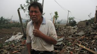 A man stands on debris of his damaged house after a tornado hit Funing county, Yancheng, Jiangsu province, China June 23, 2016. China Daily/via REUTERS EDITORS - THIS PICTURE WAS PROVIDED BY A THIRD PARTY. EDITORIAL USE ONLY. CHINA OUT. NO COMMERCIAL OR EDITORIAL SALES IN CHINA. THIS PICTURE WAS PROCESSED BY REUTERS TO ENHANCE QUALITY. AN UNPROCESSED VERSION HAS BEEN PROVIDED SEPARATELY.   TPX IMAGES OF THE DAY