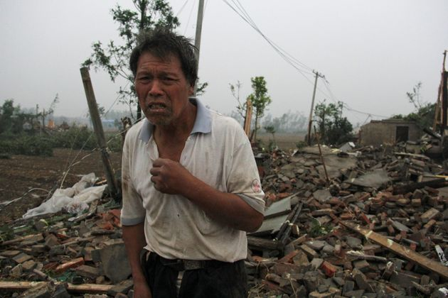 A man stands on debris of his damaged house after a tornado hit Funing county, Yancheng, Jiangsu province,...