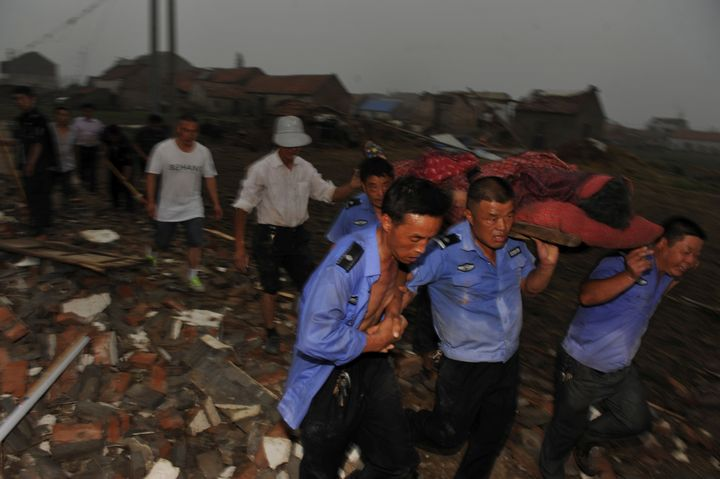 Rescue workers carry out an injured person from debris of damaged houses after a tornado hit Yancheng, Jiangsu province, Chin