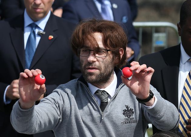 Comedian Simon Brodkin, also known as Lee Harris, hands out golf balls emblazoned with swastikas during...
