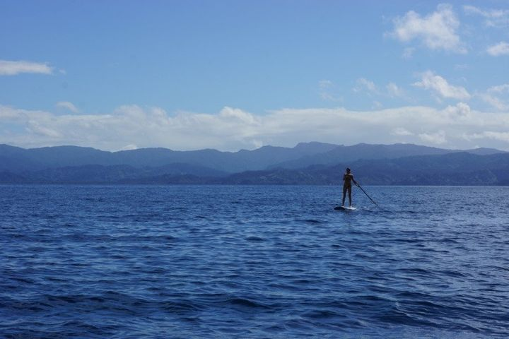 Paddle-boarding off the coast of an island in Fiji. We sailed to Fiji from New Zealand with friends. However, most of our 18 months of travel was done independently.