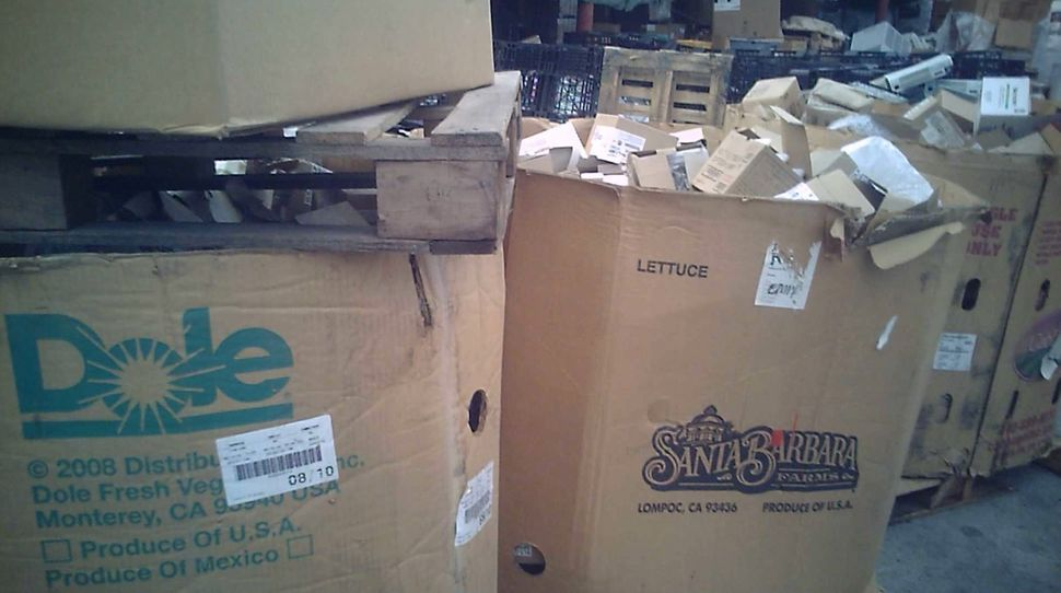 Piles of e-waste in old cardboard boxes.