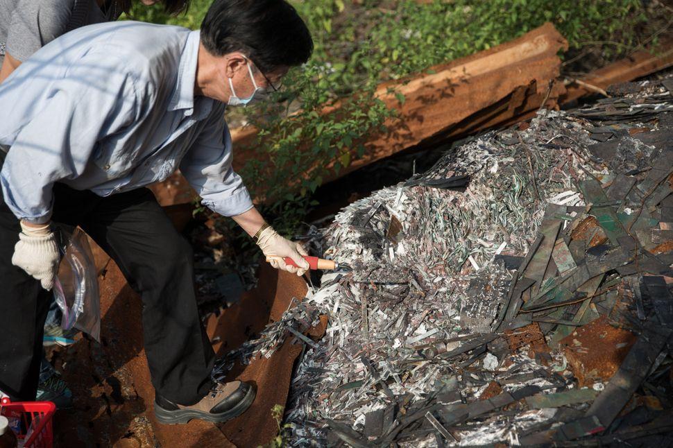 A man digs through charred e-waste near the junkyard.