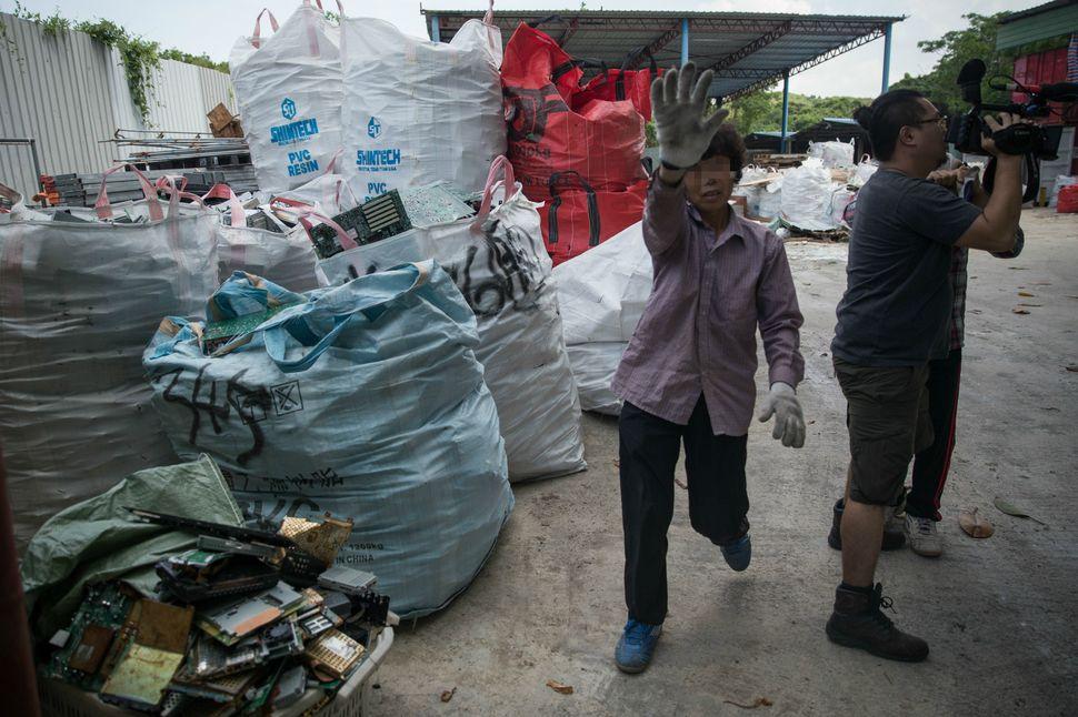 Toweringbags of e-waste ata junkyard in Hong Kong.