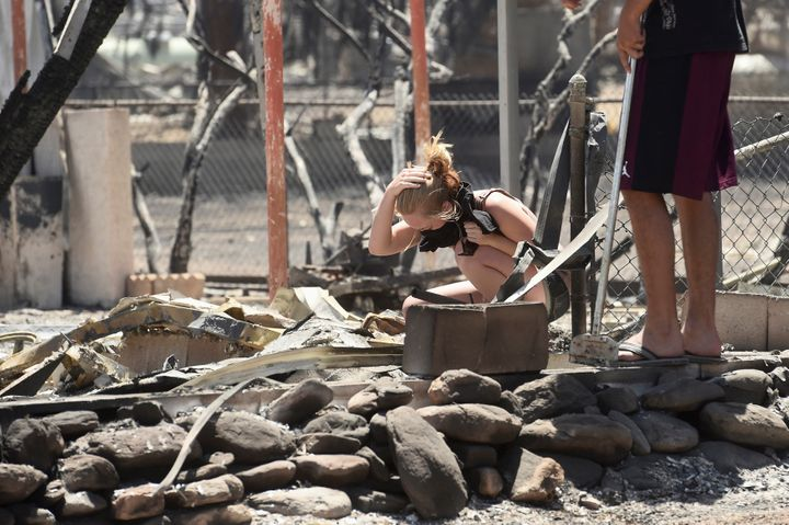 Brittany Thompson cries after finding a deceased dog at a burned down residence after the Erskine Fire burned through South L