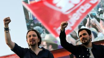 Podemos (We Can) leader Pablo Iglesias (L) and Izquierda Unida (United Left) leader Alberto Garzon, now running together under the coalition Unidos Podemos (Together We Can), lift their fists during the last campaign rally for Spain's upcoming general election in Madrid, Spain, June 24, 2016. REUTERS/Andrea Comas