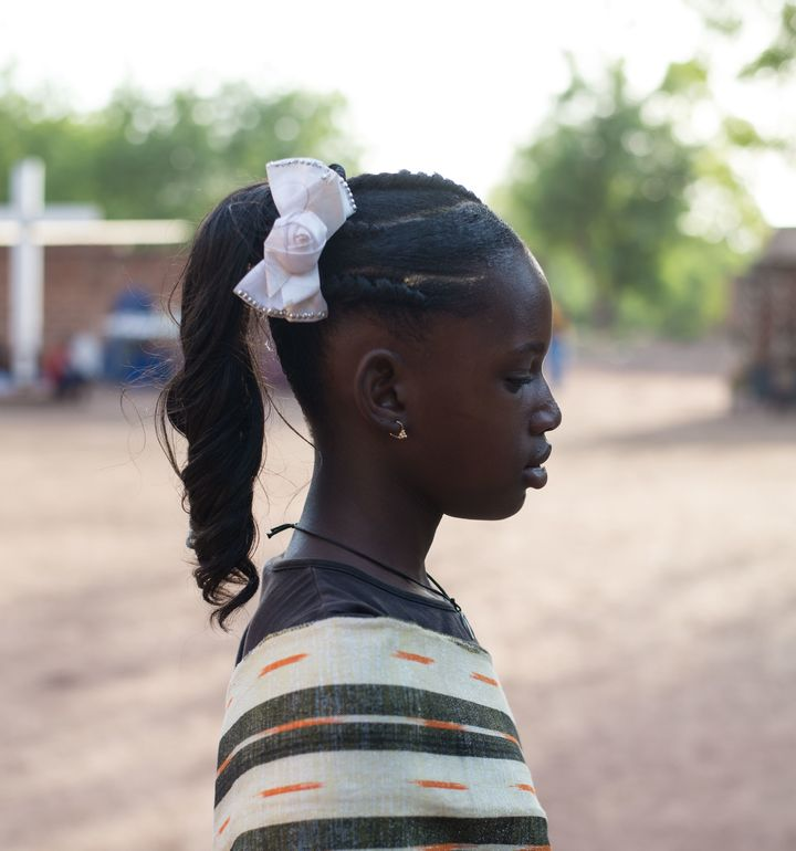<em>A young girl models a popular, heavily chemical and product-laden hair style often seen during celebrations. </em>