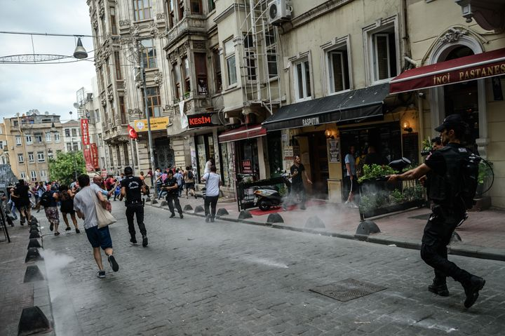 Turkish anti-riot police officers fire rubber bullets to disperse demonstrators gathered for a rally staged by the LGBT commu
