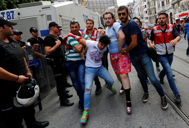Plainclothes police officers detain LGBT rights activists as they try to gather for a pride parade, which was banned by the g