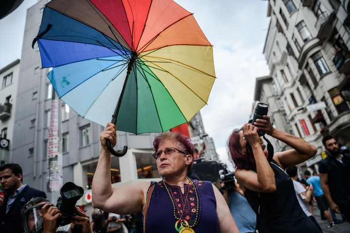 A woman holds a rainbow umbrella during a rally staged by the LGBT community on Istiklal avenue in Istanbul on June 26, 2016.