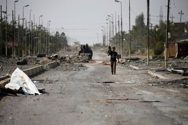 A member of Iraqi counterterrorism forces walks with his weapon in