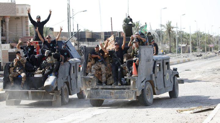 Iraqi counterterrorism forces gesture in Falluja, Iraq, June 26, 2016.