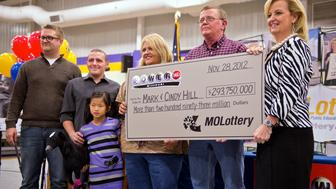 Cindy and Mark Hill, center and second from right, stand with a ceremonial check from the Missouri Lottery for $293,750,000 during the news conference, Friday, November 30, 2012, at North Platte High School in Dearborn, Missouri, after the family claimed $293,750,000 as co-winners in the Powerball lottery jackpot. At far left are sons Jarod and Cody Hill and daughter Jaiden Hill. At far right is May Scheve, director of the Missouri Lottery. (David Eulitt/Kansas City Star/MCT via Getty Images)