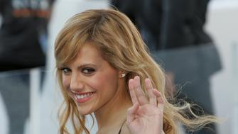 """U.S. actress Brittany Murphy waves as she arrives at the Sydney premiere of the movie """"Happy Feet"""" at Fox Studios in Sydney December 10, 2006. REUTERS/Will Burgess  (AUSTRALIA)"""