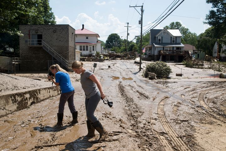 People take pictures of the mud covering the front of their home and a street intersection on June 25, 2016 in Clendenin, Wes