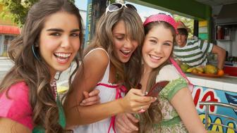 Close-up of a teenage girl holding a mobile phone and standing at the juice bar with her friends