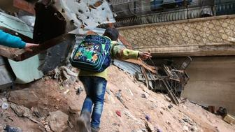 A school-aged child navigates through rubble and barbed wire in Aleppo, Syria, Feb. 11, 2016.