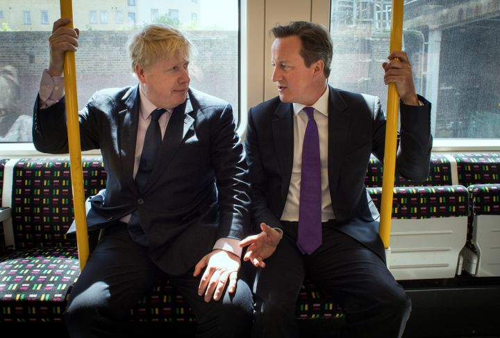 Britain's Prime Minister David Cameron and Boris Johnson sit on an underground train as they head to Westminster after local