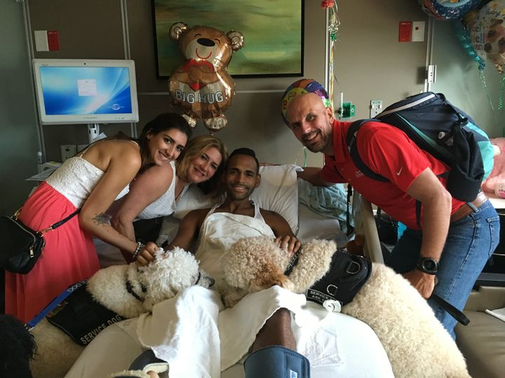 Boston survivors along with service dogs Koda and Zealand posewith Pulse survivor Angel Colon.