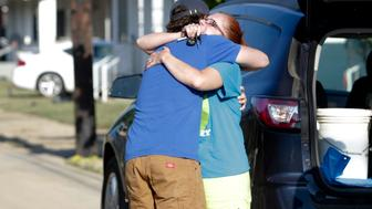 Ami Palmer, 40, hugs her nephew Landon Palmer (L), upon returning to her home after flooding damaged her home in Clendenin, West Virginia, U.S., June 26, 2016.   REUTERS/Marcus Constan