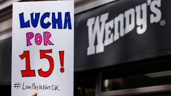 "A protester holds up a placard during a gathering outside a Wendy's fast food restaurant in support of a nation-wide strike and protest to raise the hourly minimum wage of fast food workers to $15 in San Diego, California December 5, 2013. Fast-food workers in hundreds of U.S. cities staged a day of strikes and rallies on Thursday to demand higher wages, saying the pay was too low to feed a family and forced most to accept public assistance. The sign reads, ""Fight for 15"".  REUTERS/Mike Blake  (UNITED STATES - Tags: FOOD BUSINESS CIVIL UNREST EMPLOYMENT)"