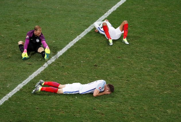 Several of England's soccer players, including goalkeeper Joe Hart (top left), are seen looking dejected...