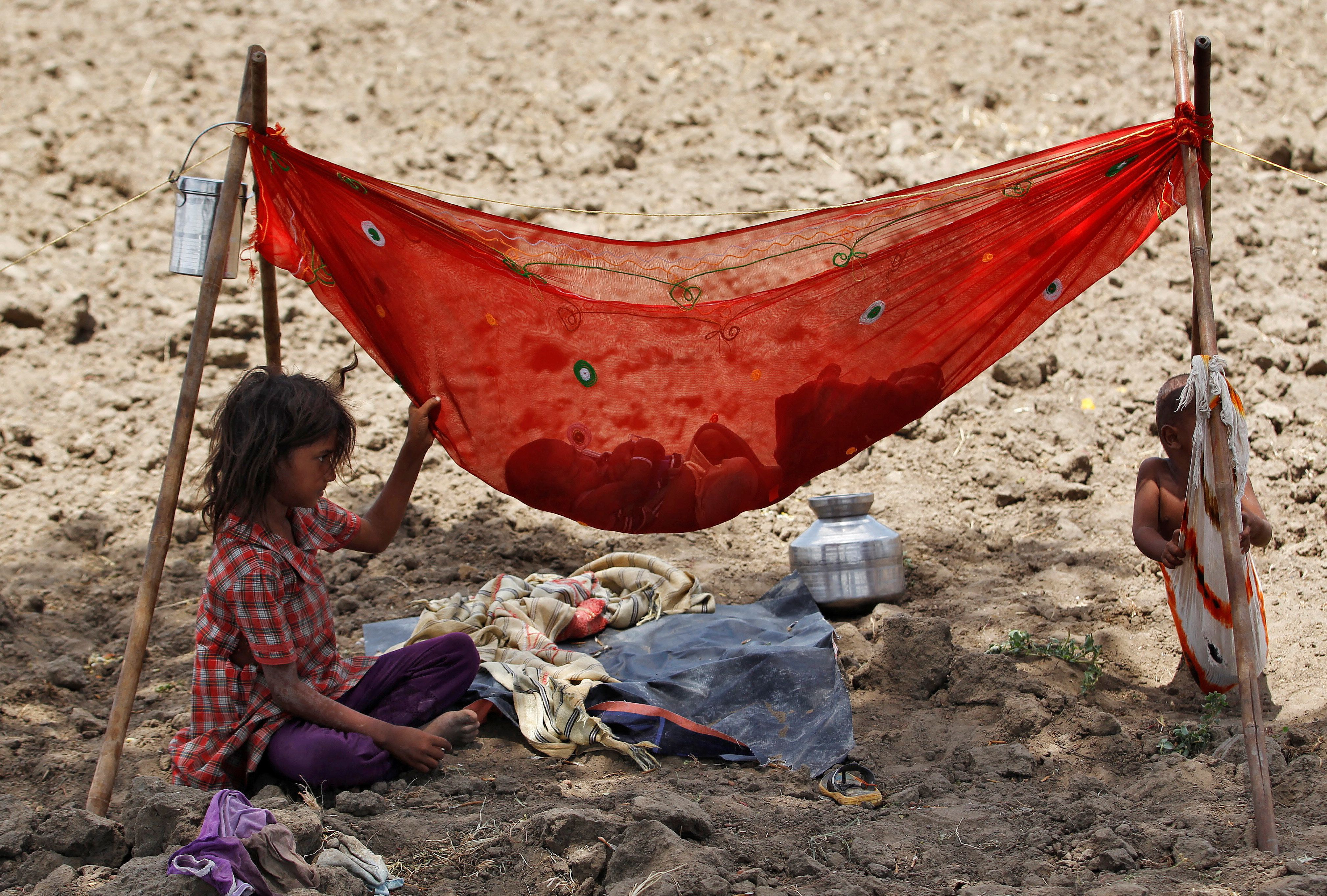 A girl sits next to her sibling who is resting in a hammock under the shade of a tree in a field on the outskirts of Ahmedabad, India May 31, 2016. REUTERS/Amit Dave