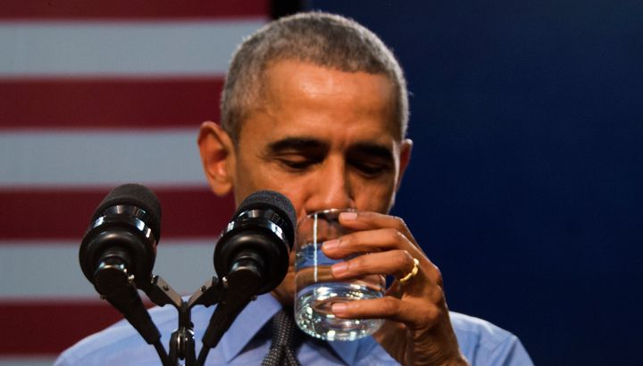 President Barack Obama drinks a glass of water as he speaks at Flint Northwestern High School in Flint, Michigan, on May 4.