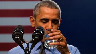 US President Barack Obama drinks a glass of water as he speaks at Flint Northwestern High School in Flint, Michigan, May 4, 2016 after meeting with locals for a neighborhood roundtable on the drinking water crisis. / AFP / Jim Watson        (Photo credit should read JIM WATSON/AFP/Getty Images)