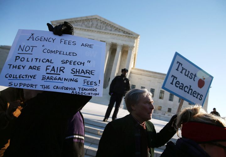 People for and against unions hold up signs in front of the Supreme Court building on Jan. 11, 2016, in Washington, D.C.
