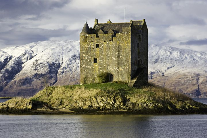 Scotland's Castle Stalker on Loch Linnhe, surrounded by snow covered mountains.