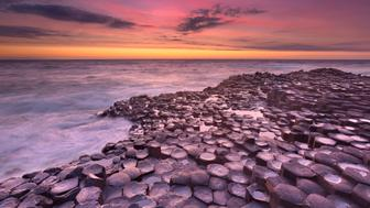 Sunset over the basalt rock formations of Giant's Causeway on the north coast of Northern Ireland.