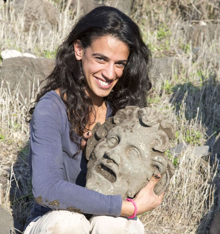 A participant of the Hippos-Sussita excavation holds an ancient bronze mask believed to depict the pagan god Pan.