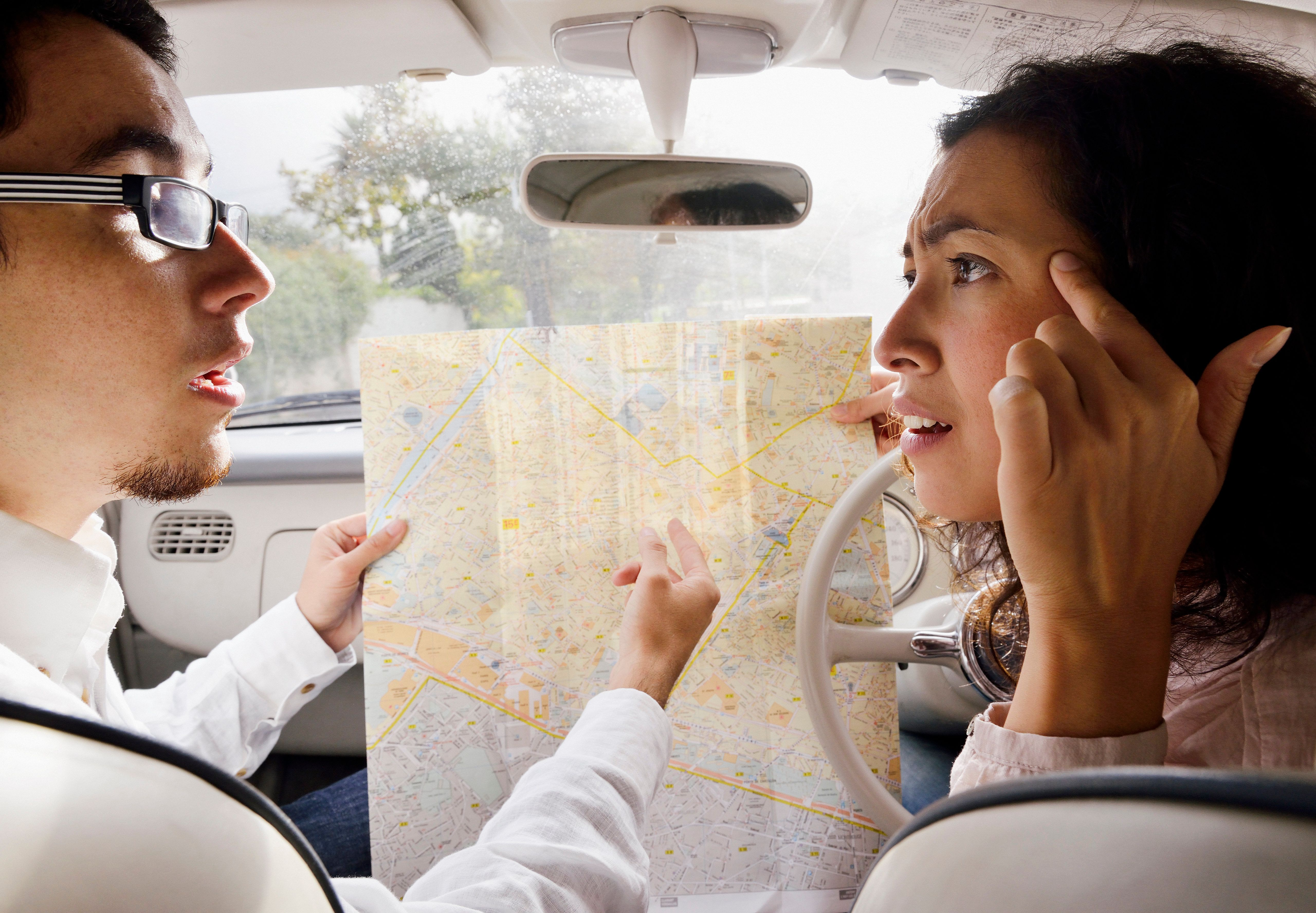 Couple in a car arguing over a map