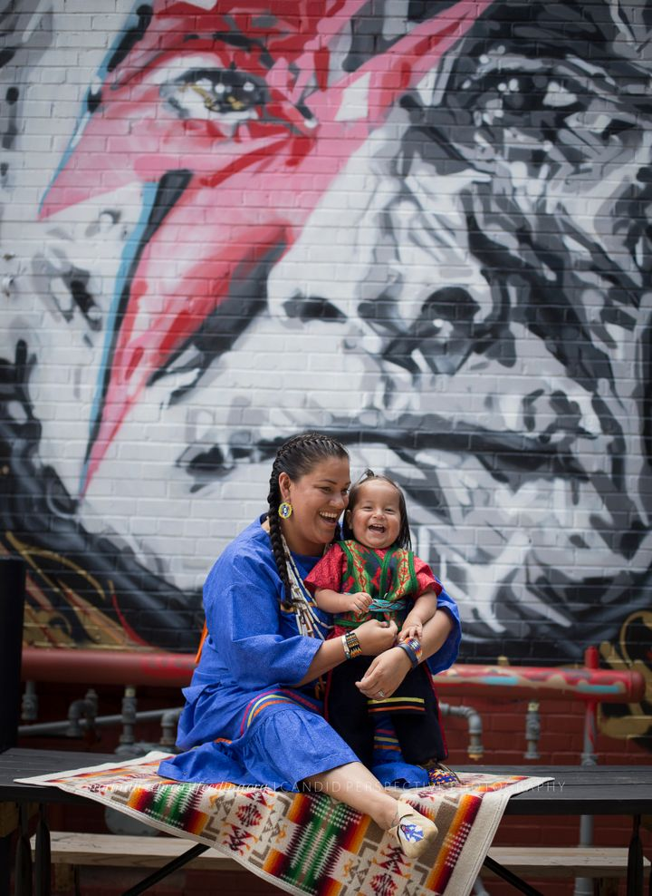 Simmons photographed Enedina Banks in front of a mural of a Native American man.