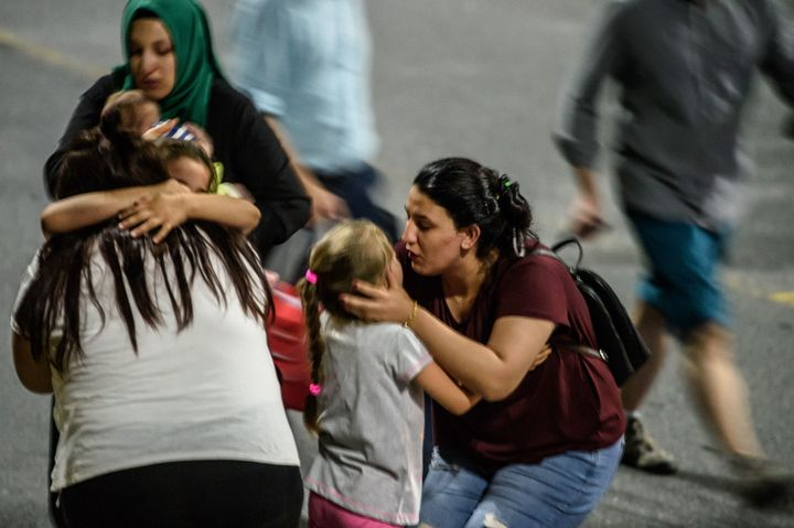 Children and their relatives embrace as they leave Ataturk airport.